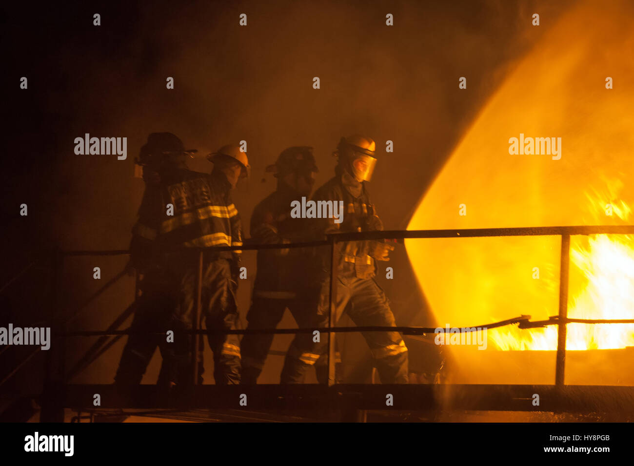 Firefighters using full spray to put out fire during firefighting exercise - Stock Image
