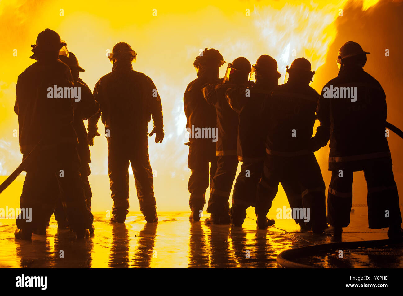 Group of eight firefighters during fire fighting exercise - Stock Image