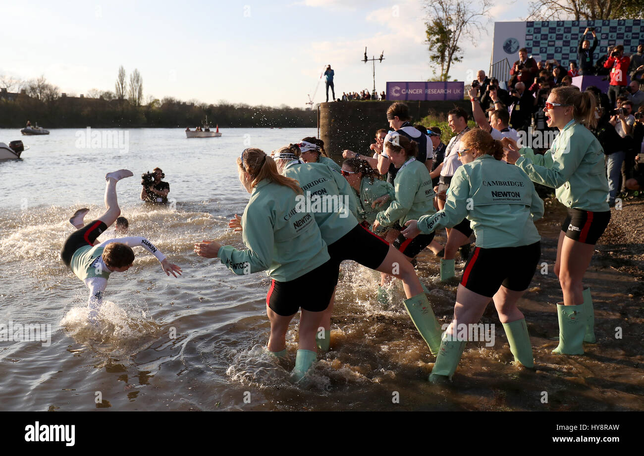 Cambridge Women's Matthew Holland (left) is thrown into the water after the Women's Boat Race on the River Thames, Stock Photo