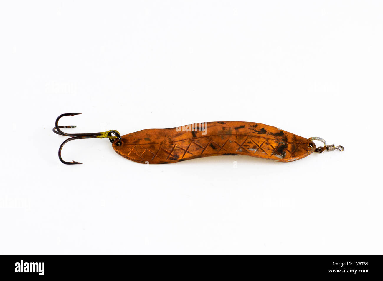 Exhibition of self-made fishing metal lures. Bait for fishing in the shape of a spoon with a hook on a white background. Stock Photo