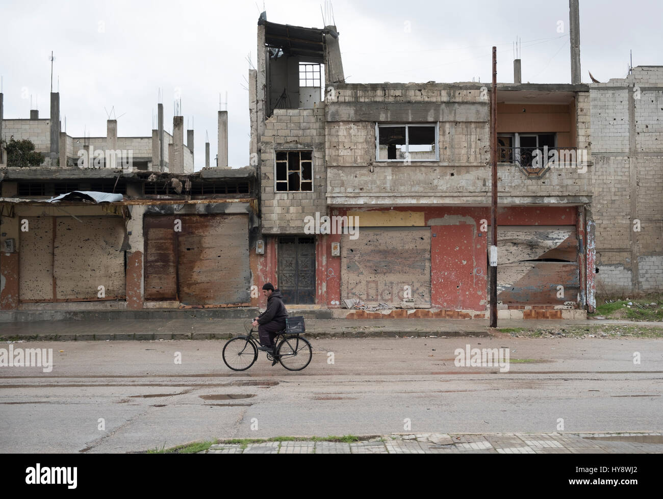 Bicycler in distressed district Amr in Homs, Syria in early 2017 - Stock Image