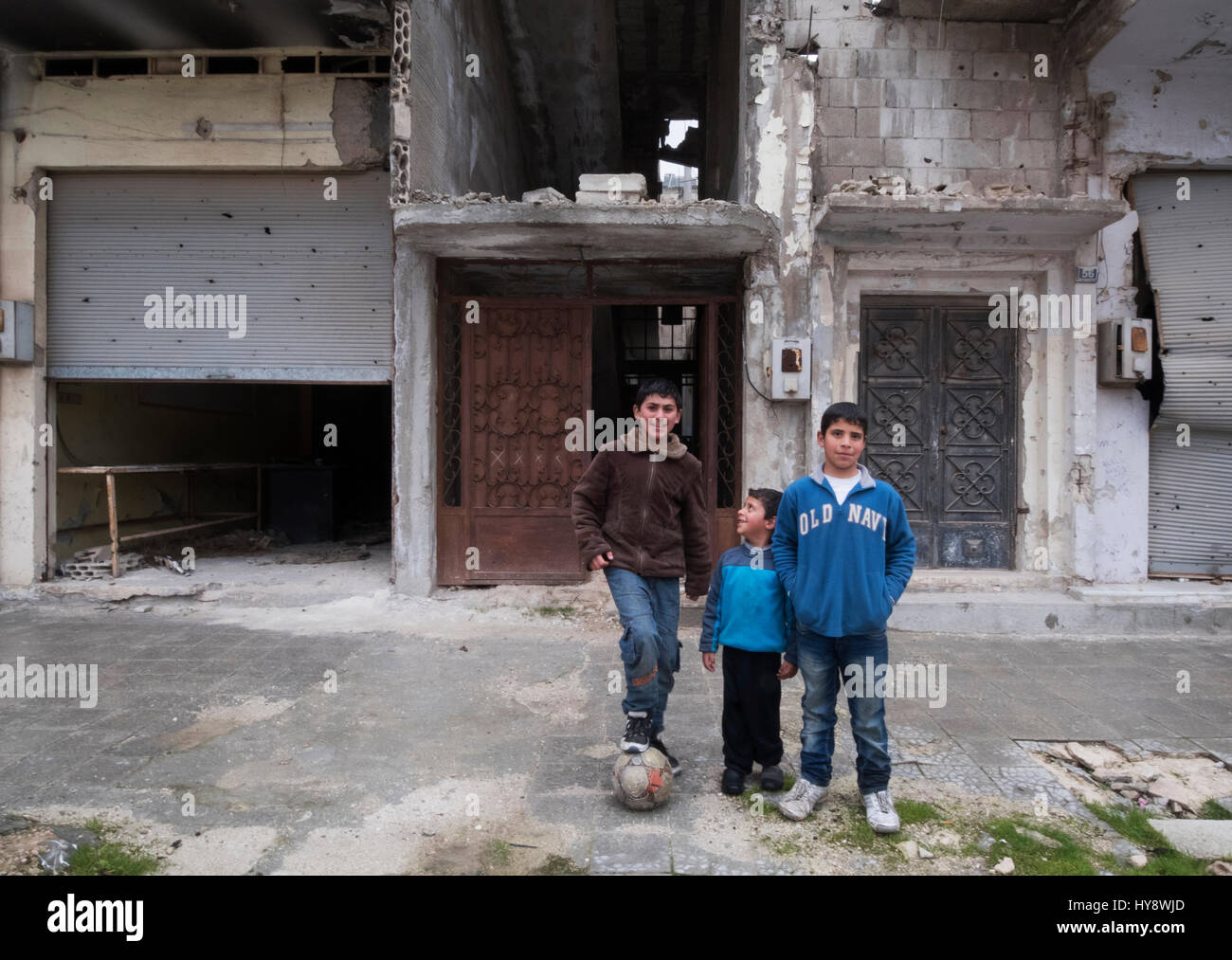 Children playing football in distressed district Baba Amr, Homs, Syria in early 2017 - Stock Image