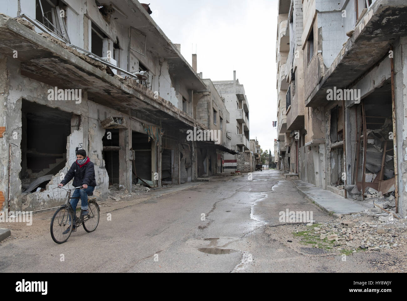 Bicycler in distressed district Baba Amr in Homs, Syria in early 2017 - Stock Image
