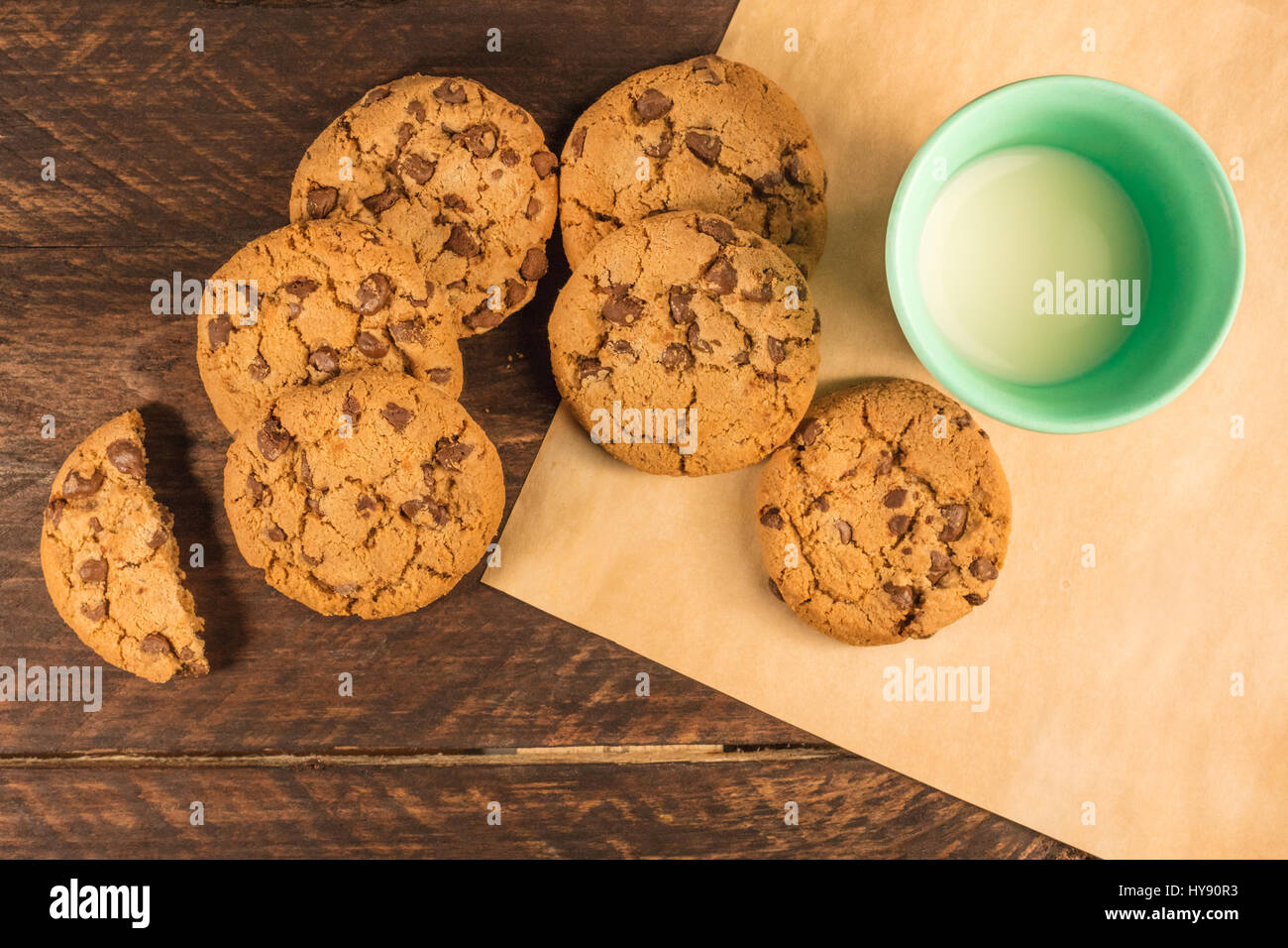 Chocolate chips cookies on baking paper, with milk - Stock Image