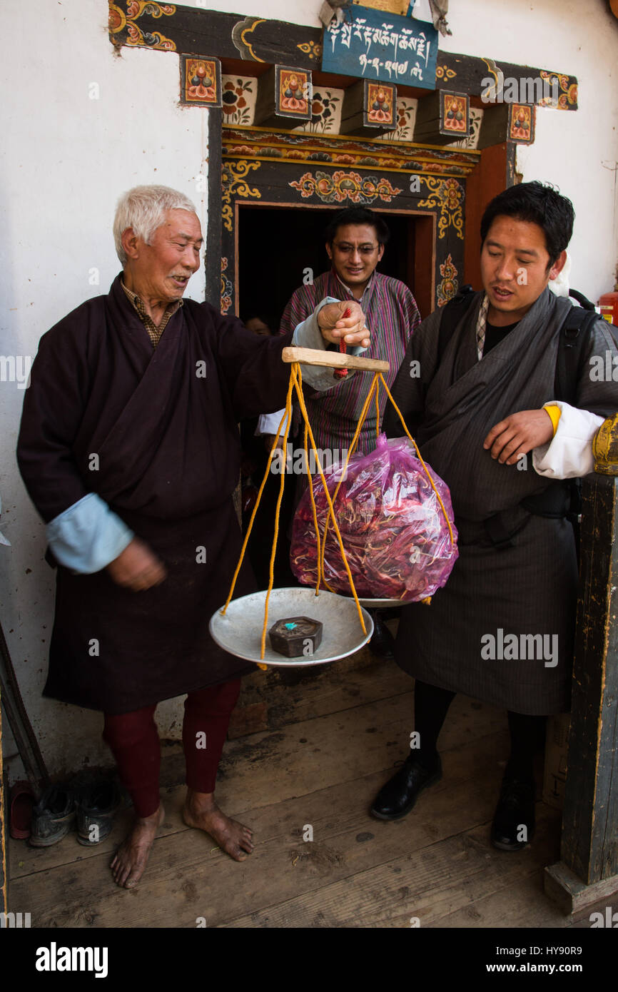 A young man buying peppers from an old farmer in traditional Bhutanese dress.  Tamchog, Bhutan. - Stock Image
