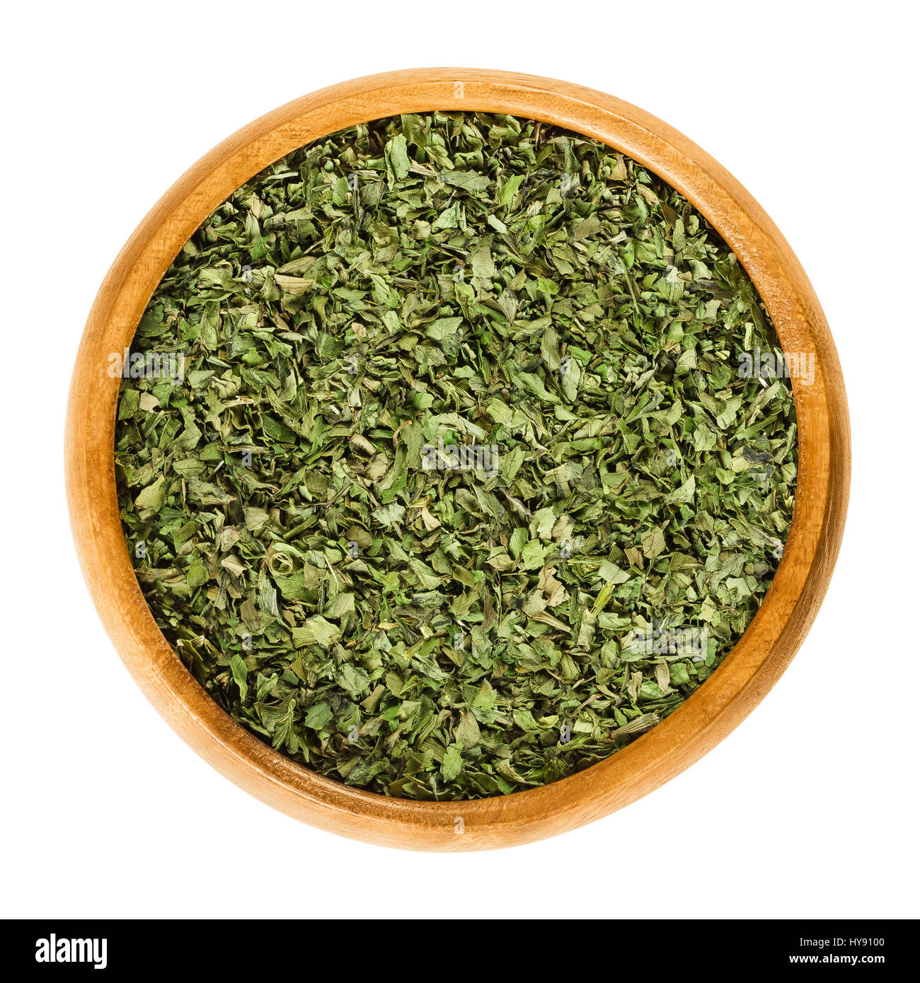 Dried and grated lovage leaves in wooden bowl. Edible green herb and vegetable, used in salads and soups. Levisticum - Stock Image