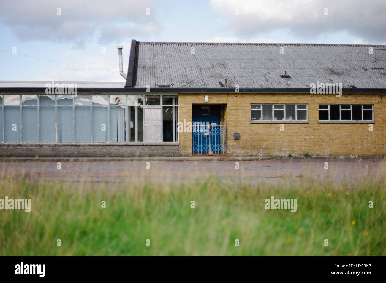 Boarded-up commercial building showing tough economic times. - Stock Image