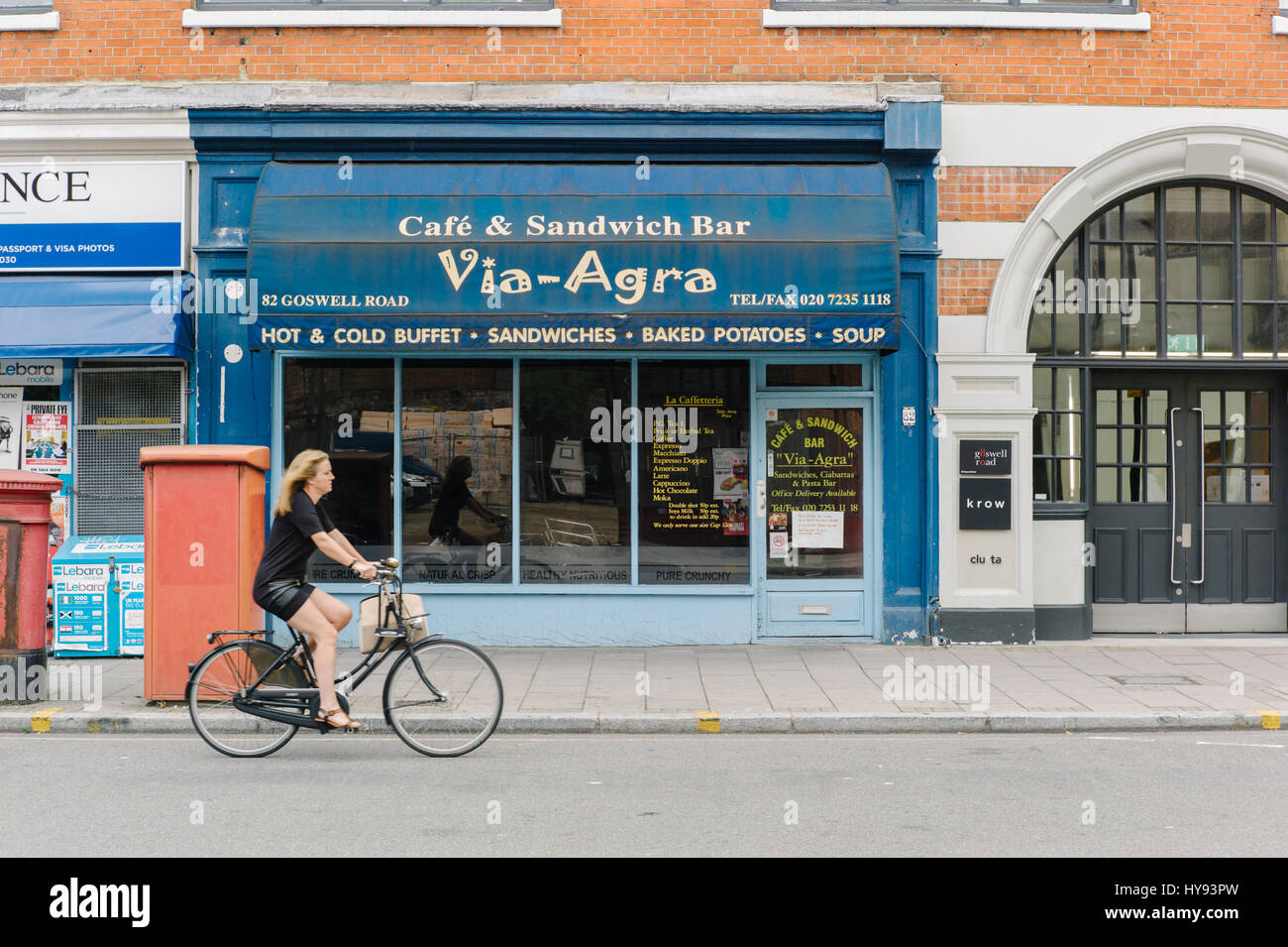 Young woman in skirt on bike, on a city street. - Stock Image