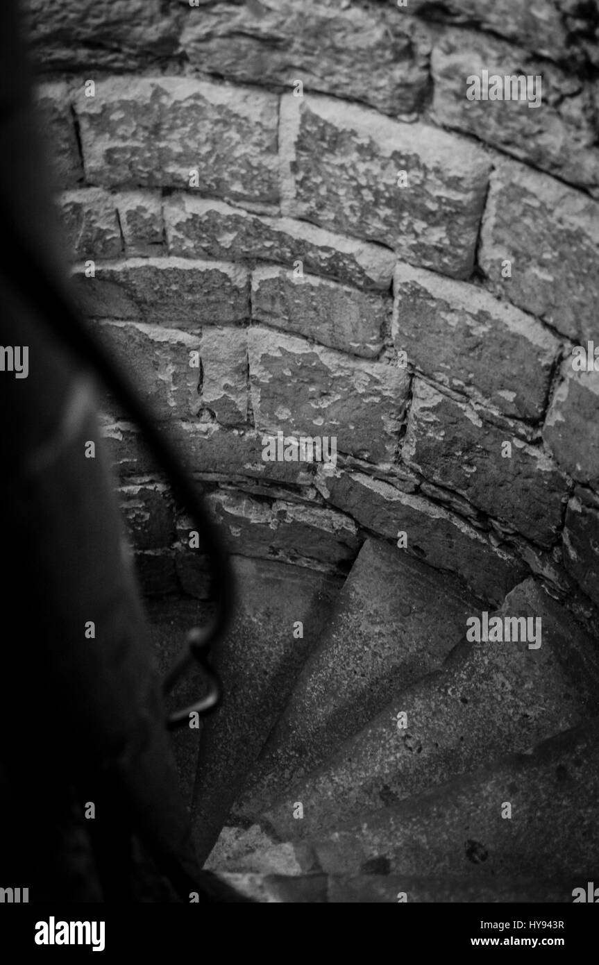 An old eerie stone stairwell leading downwards in black and white. - Stock Image