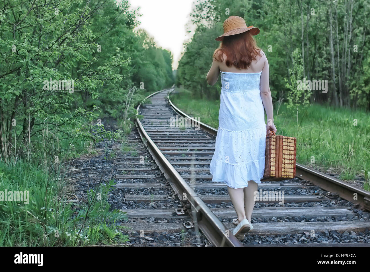 girl in a white sundress and wicker suitcase walking on rails Stock Photo