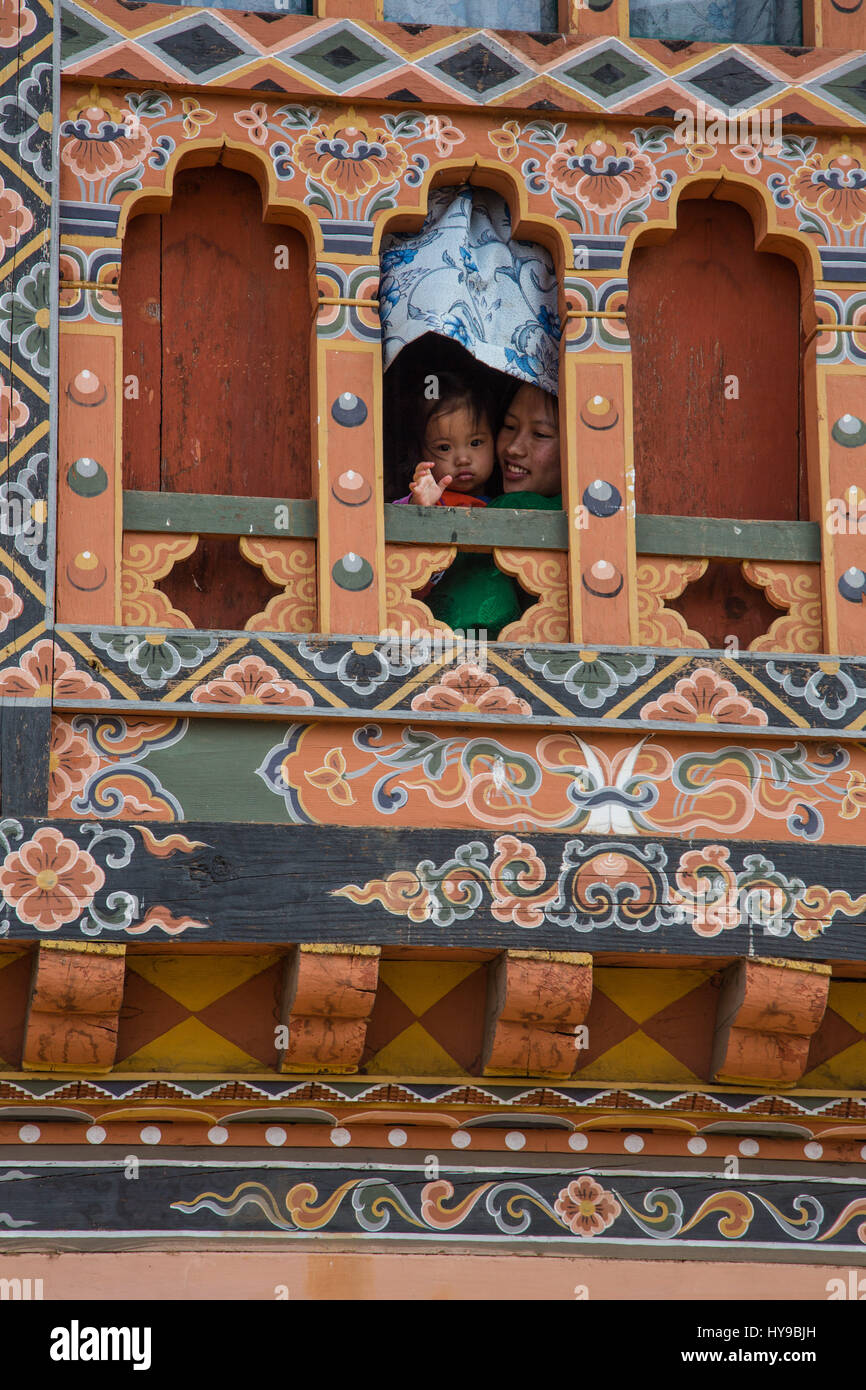 A small child her mother look out a window in Punakha, Bhutan.  The window is traditional Bhutanese architecture - Stock Image