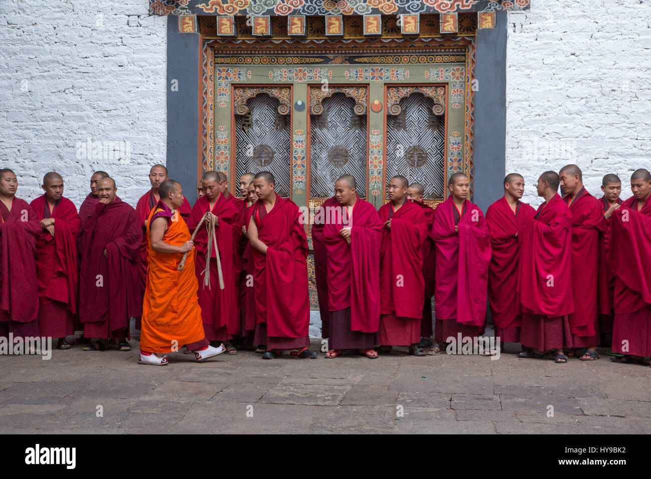 A line of Buddhist monks gather for a ceremony in the religious courtyard of the Punakha Dzong in Punakha, Bhutan. - Stock Image