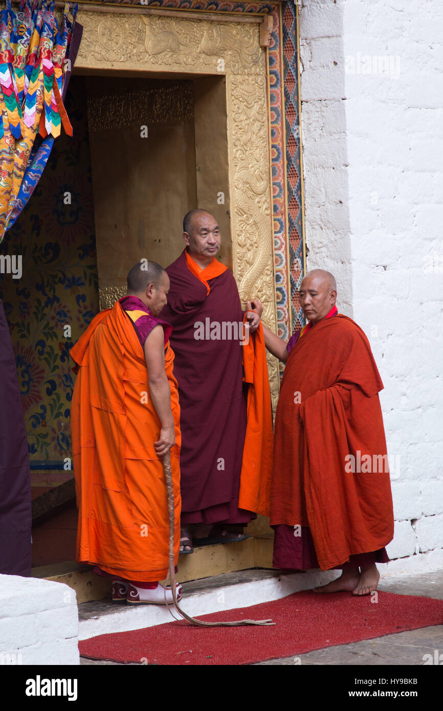 The head abbot talks with two other monks before a ceremony in the Punakha Dzong, Punakha, Bhutan. - Stock Image