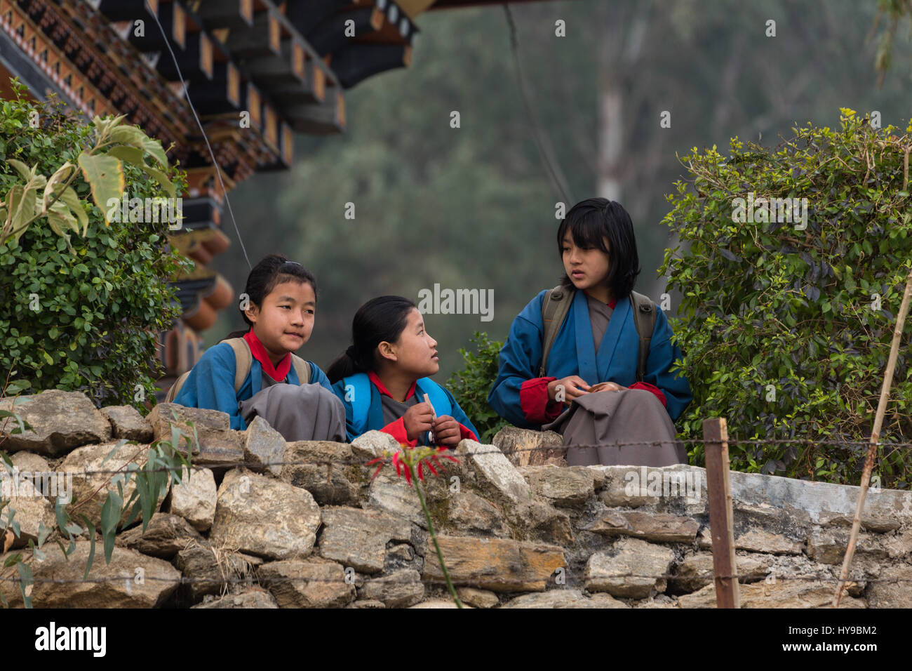 Three teen-age schoolgirls in traditional kira skirts and tego jackets visit before school in Punakha, Bhutan. - Stock Image