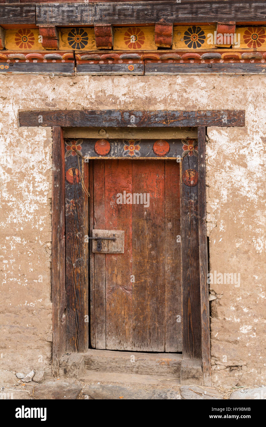 Traditional Bhutanese farm houses are built of packed mud, with very thick walls.  Punakha, Bhutan.  Detail of door. - Stock Image