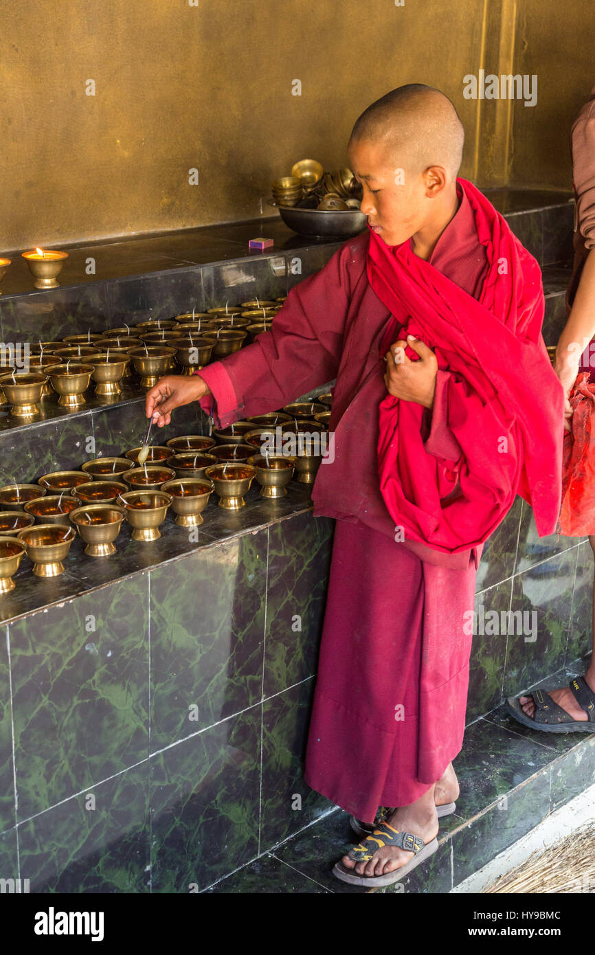 A young Buddhist monk prepares butter lamps at the Punakha Stupa in Punakha, Bhutan. - Stock Image