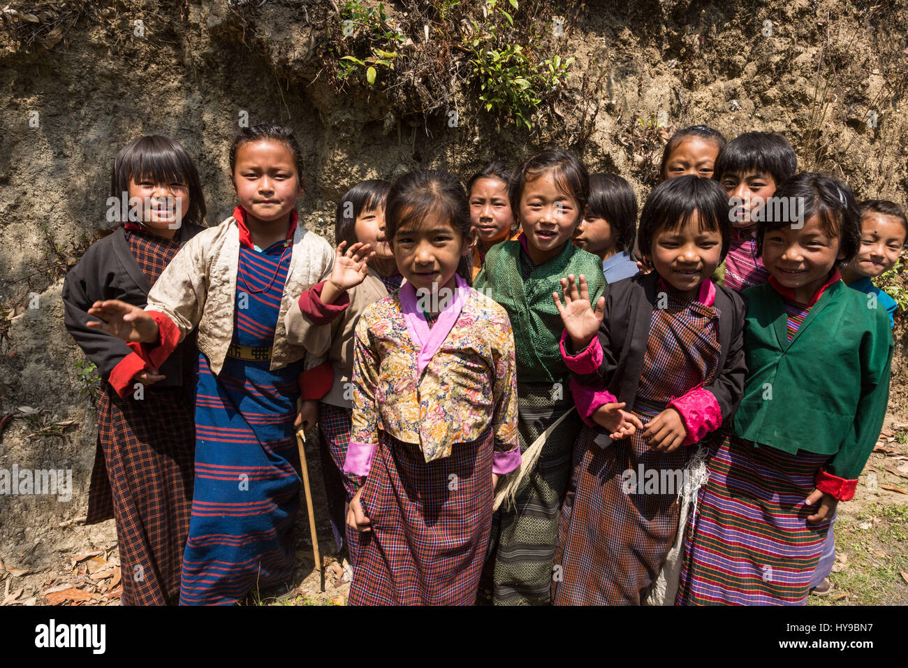 Young schoolgirls in traditional kira skirts and tego jackets pose for their picture by the road in Talo, Bhutan. - Stock Image