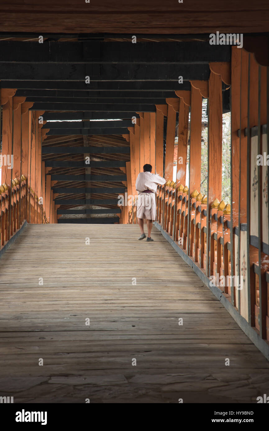 A Bhutanese man in the traditional gho robe crosses the covered bridge of the Punakha Dzong, Punakha, Bhutan. - Stock Image