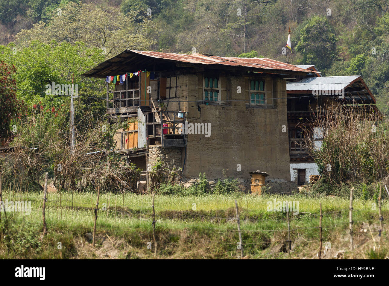 Traditional Bhutanese farm houses are built of packed mud, with very thick walls.  Punakha, Bhutan.  The ground - Stock Image