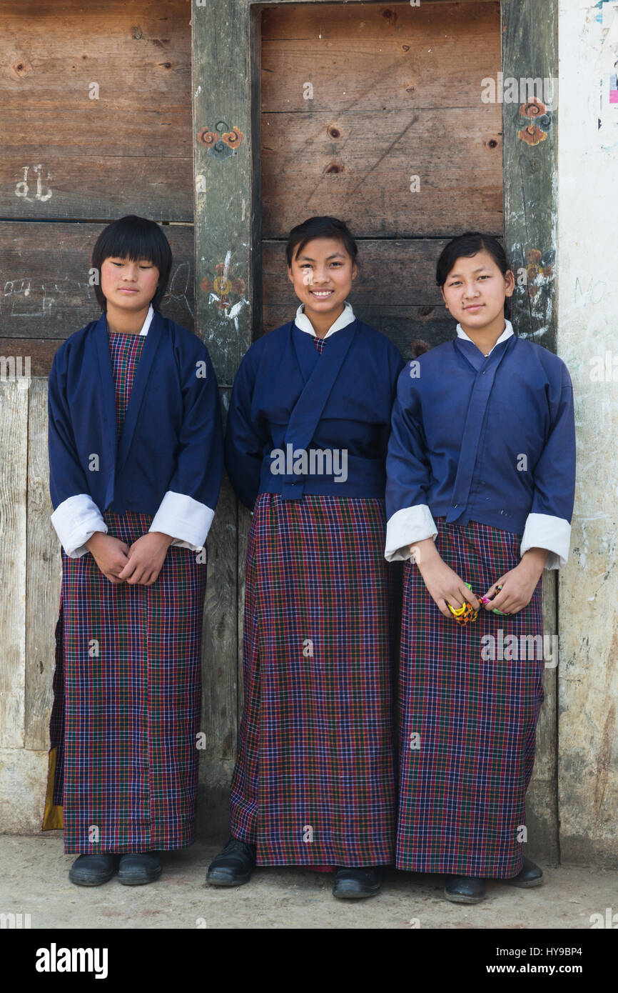 Three young girls in school uniforms of the traditional kira skirt and tego jacket.   Punakha, Bhutan. - Stock Image