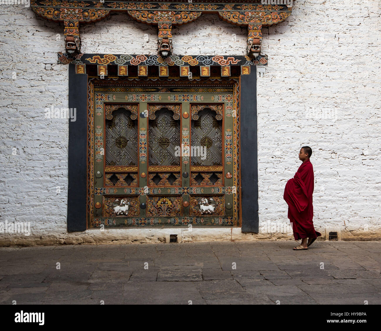 A Buddhist monk in the courtyard of the Punakha Dzong, Punakha, Bhutan. - Stock Image