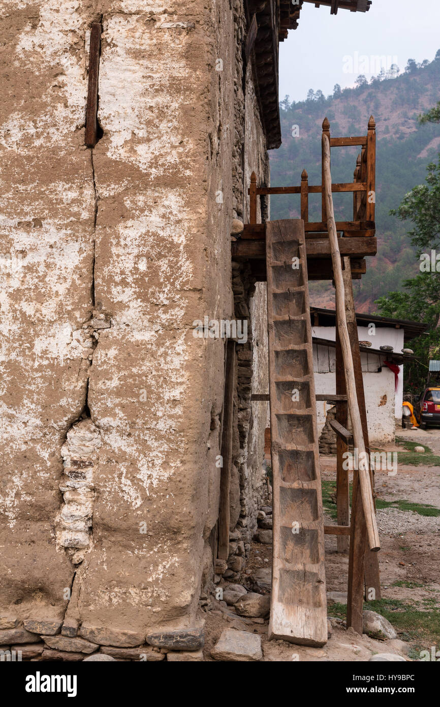 Traditional Bhutanese farm houses are built of packed mud, with very thick walls.  The ground floor served as a - Stock Image