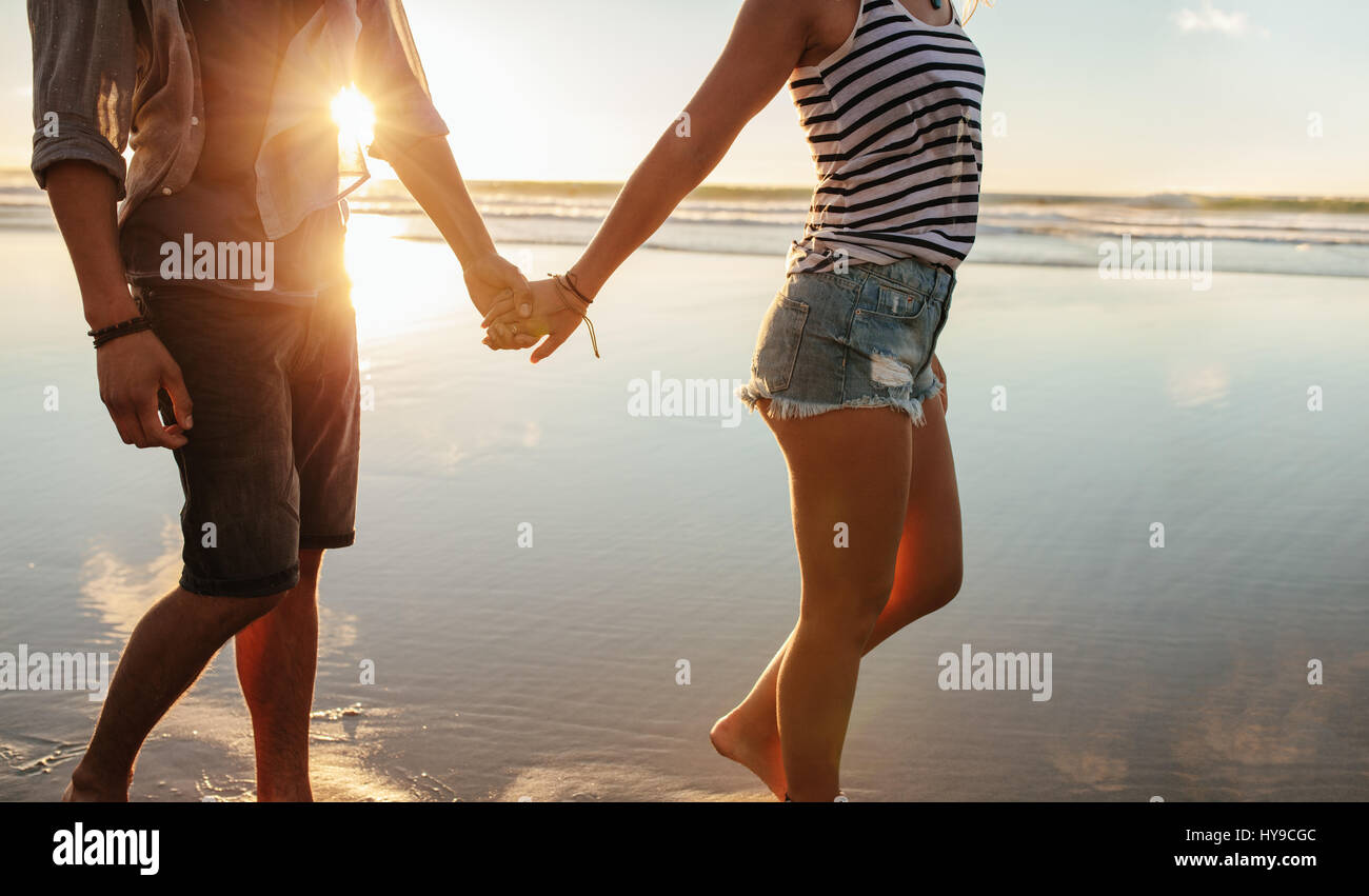 Cropped shot of young couple holding hands and walking on the beach. Loving man and woman strolling on the shore. - Stock Image