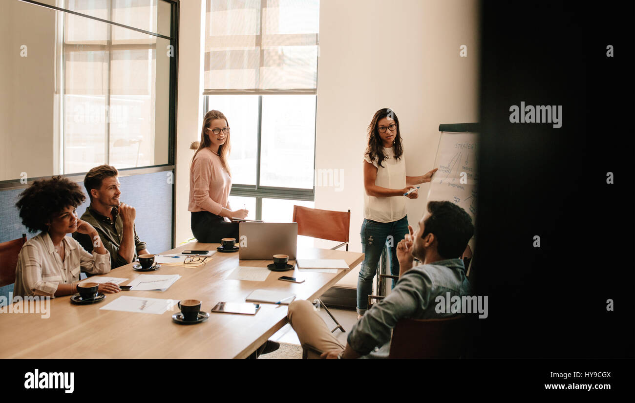 Female executive explaining new business strategy to colleagues in conference room. Business people discussing in - Stock Image