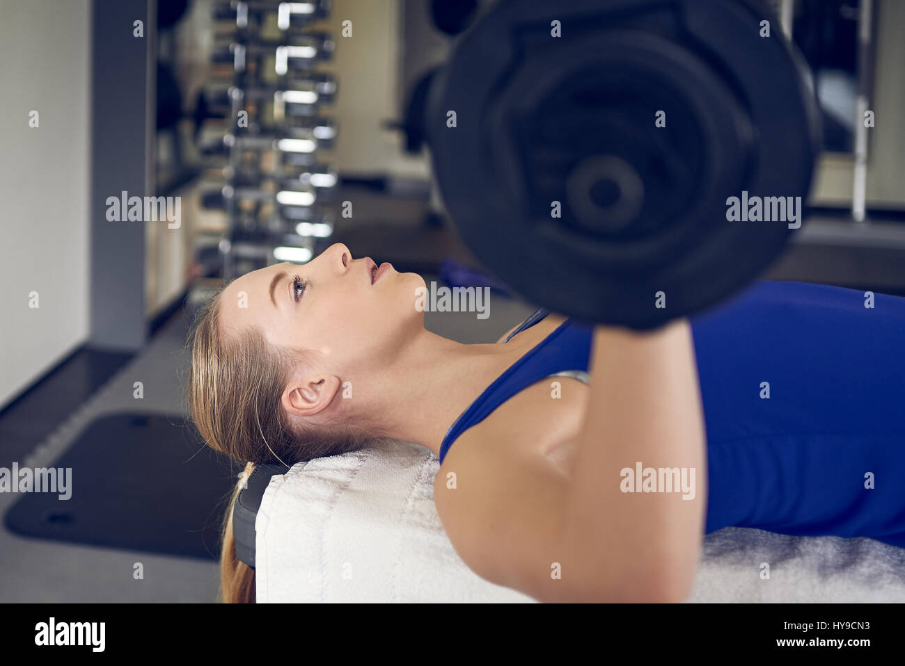 Close-up side view of young blonde woman in blue top doing bench pressing exercise with bar-bell in gym - Stock Image