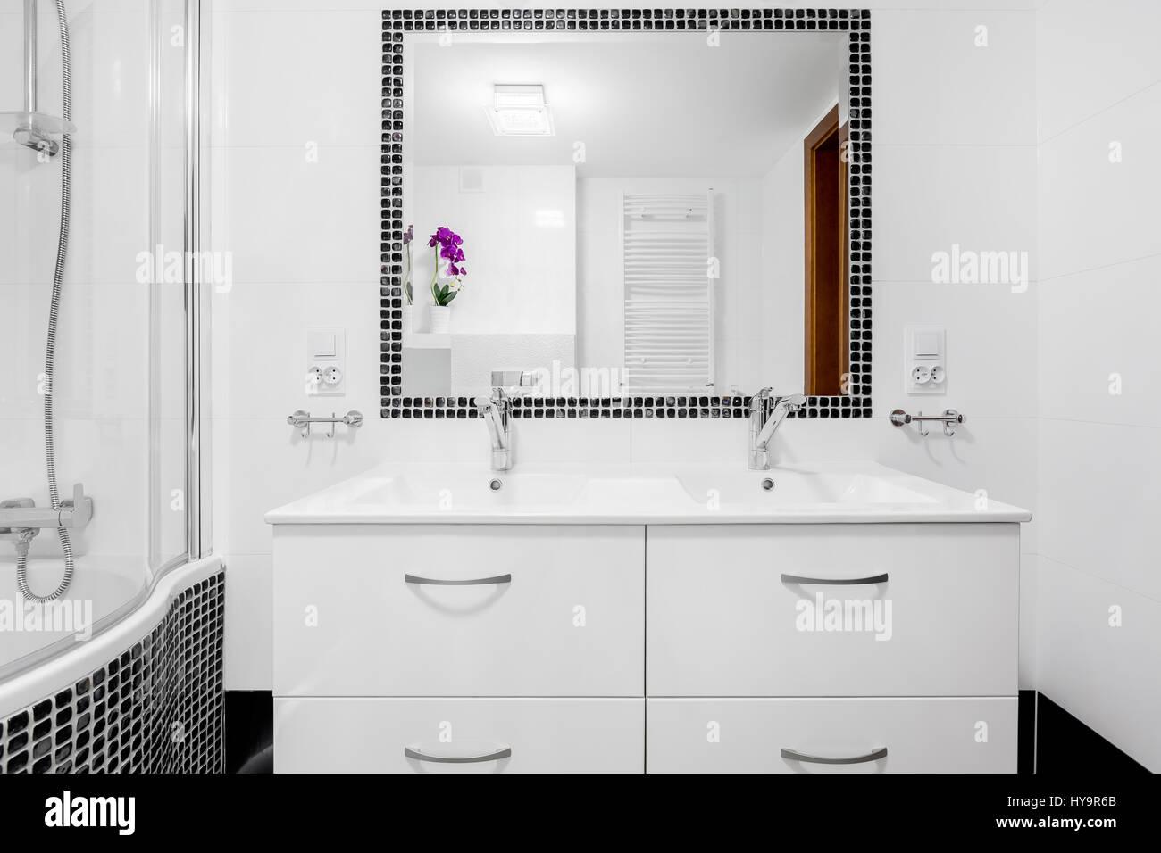 White, modern villa bathroom with basin cabinet, mirror and bathtub ...