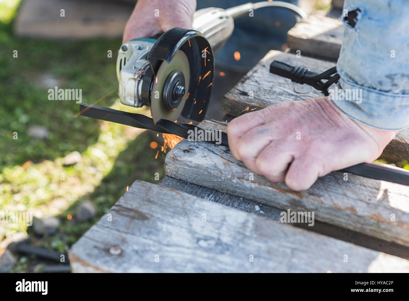 The process of cutting metal using the angle grinder. - Stock Image