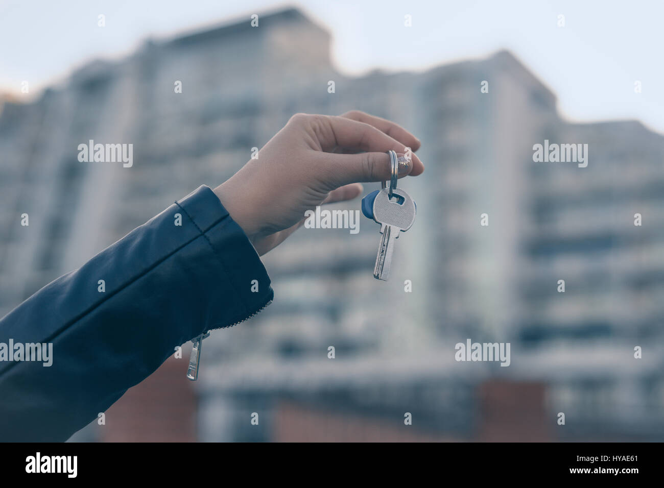 Hand holding key with modern building on background. Buying new home or flat concept. Stock Photo