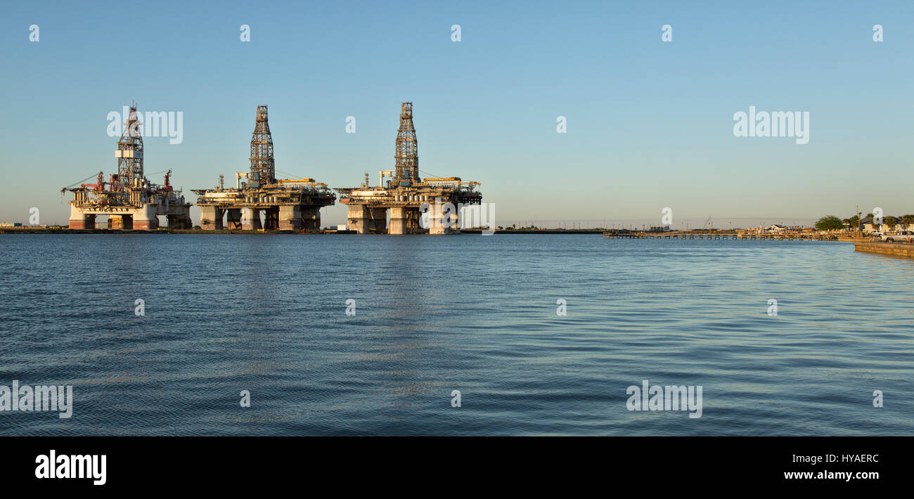 Deep water drill rigs temporarily in storage,  pm light, Harbor Island,  Canyon Port, Port Aransas to the right. Stock Photo