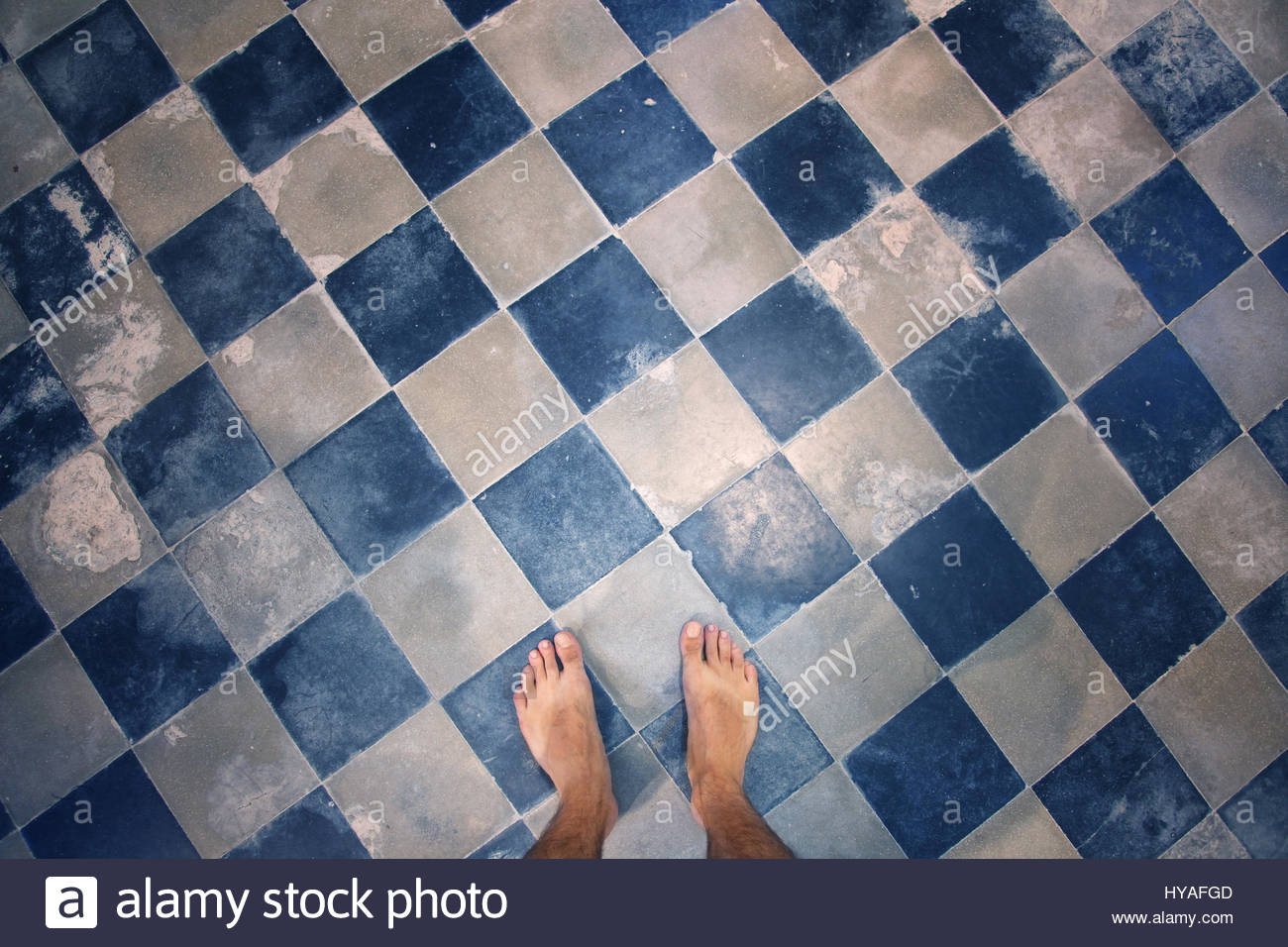 Close up of barefoot man\'s feet at blue colored mosaic aged ceramic ...