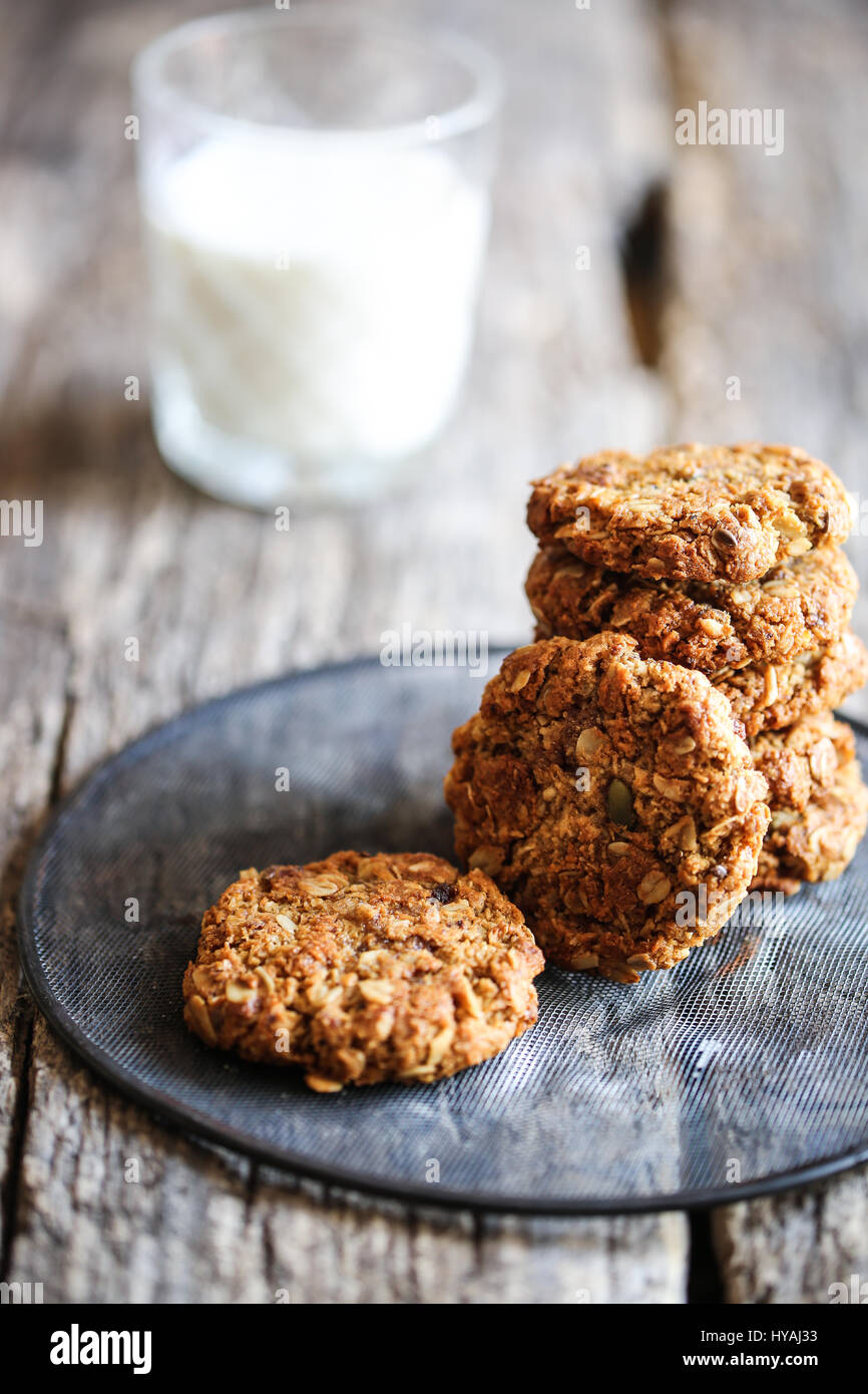 traditional anzac oat cookies and glass of milk on a wooden background Stock Photo