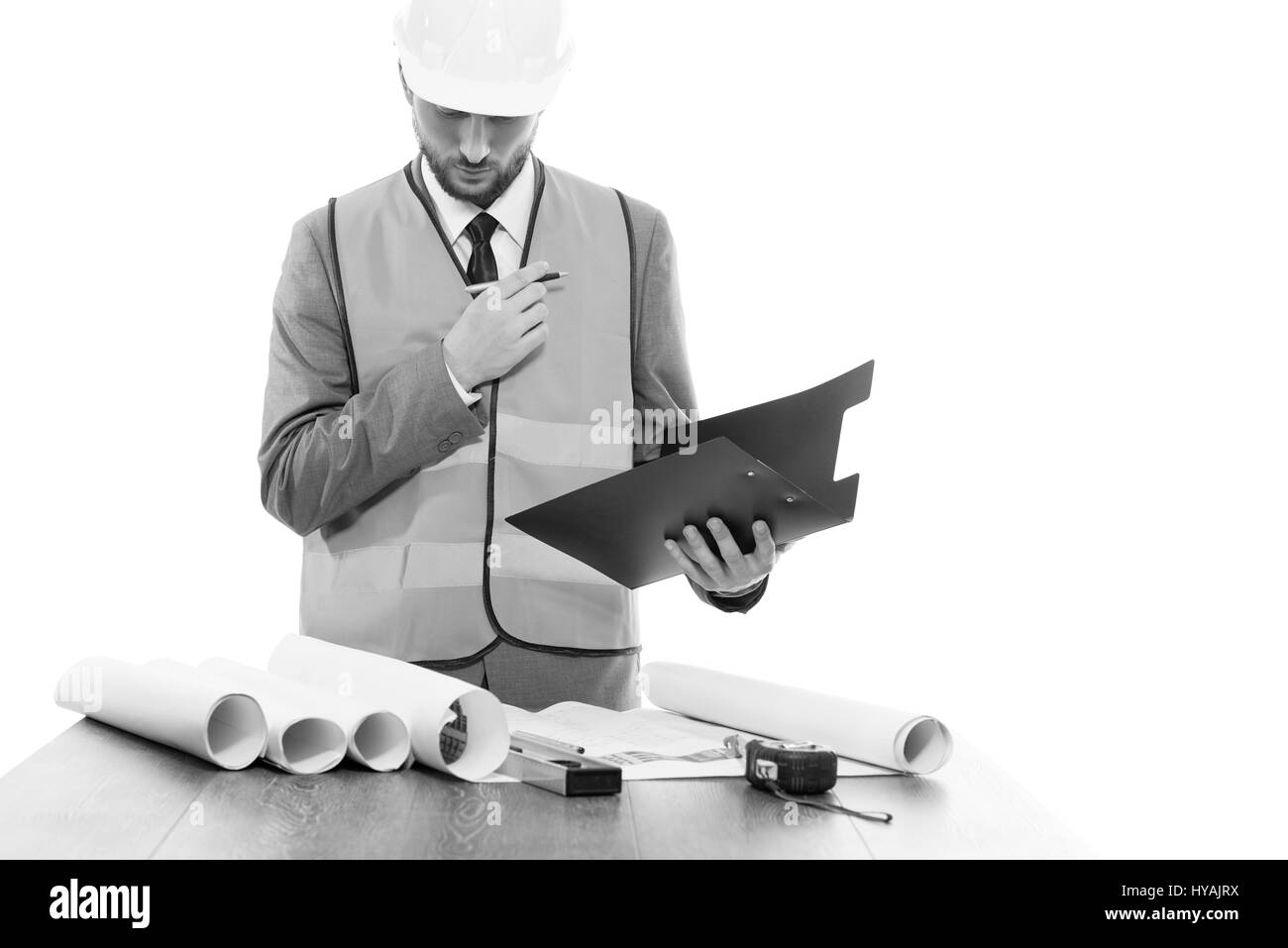 Male engineer in a protective helmet and a safety west in studio - Stock Image