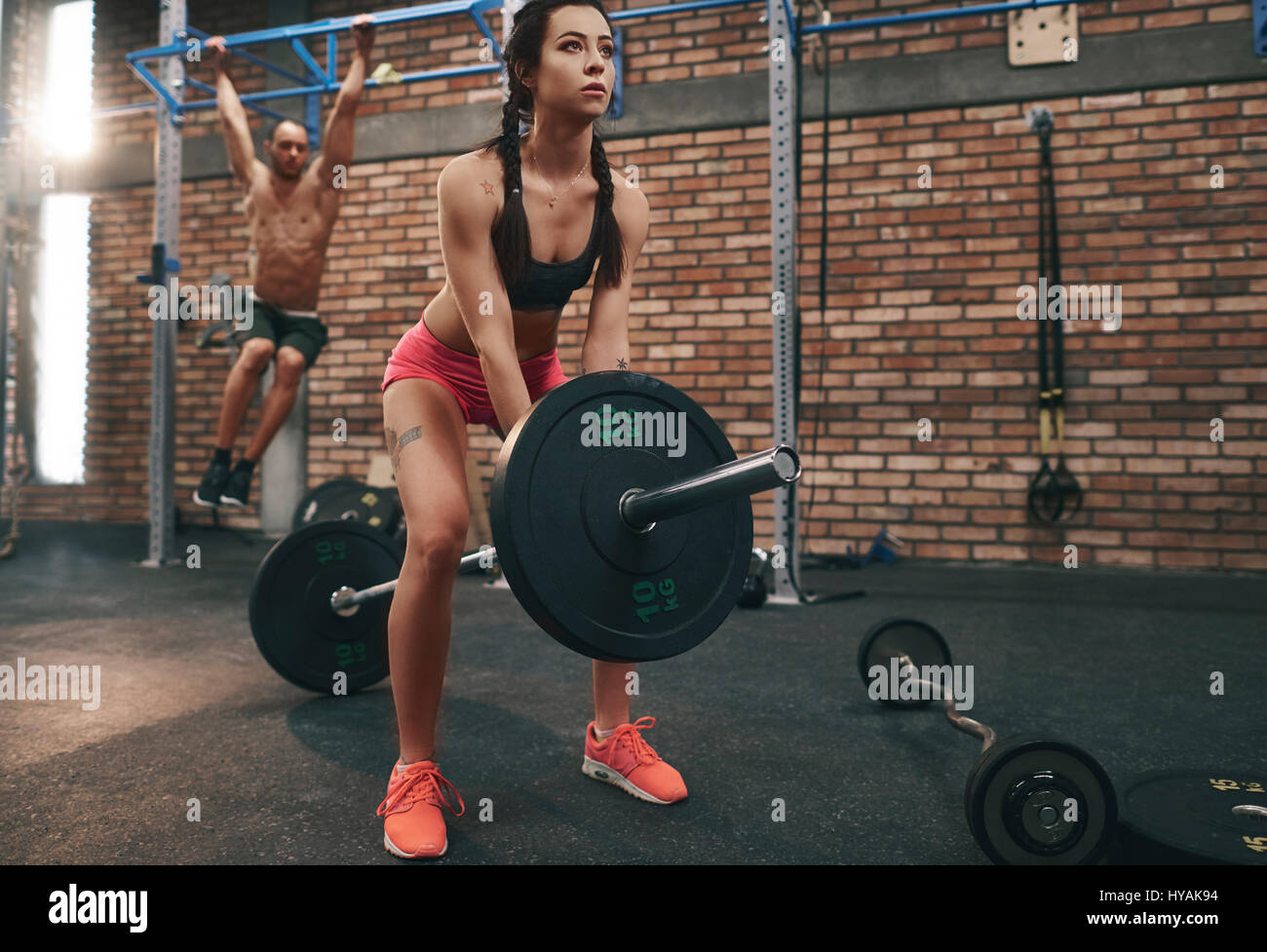 Woman preparing to lift barbell in gym - Stock Image
