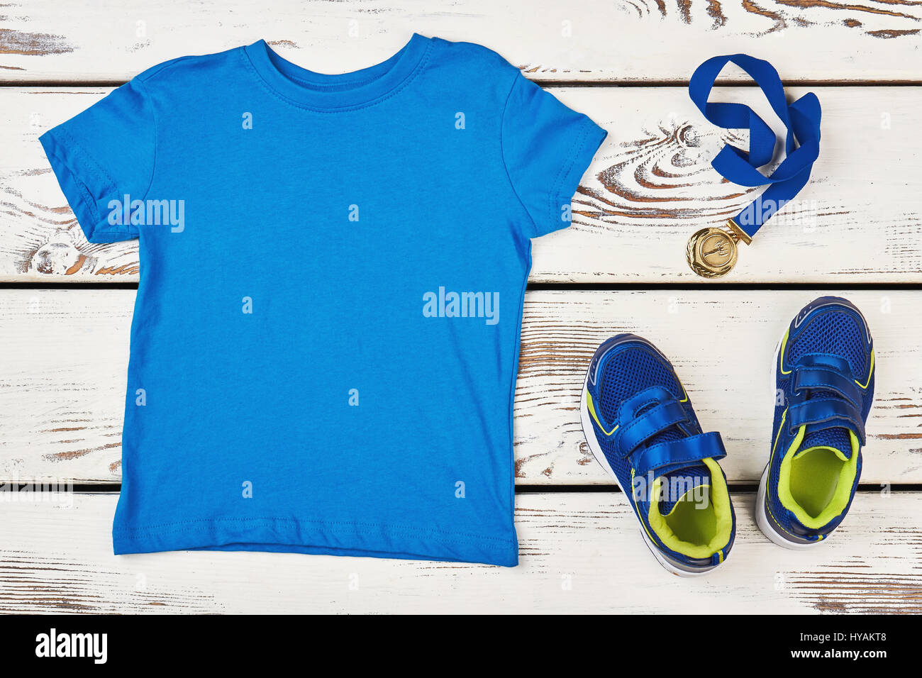 T-shirt, sneakers and medal. - Stock Image