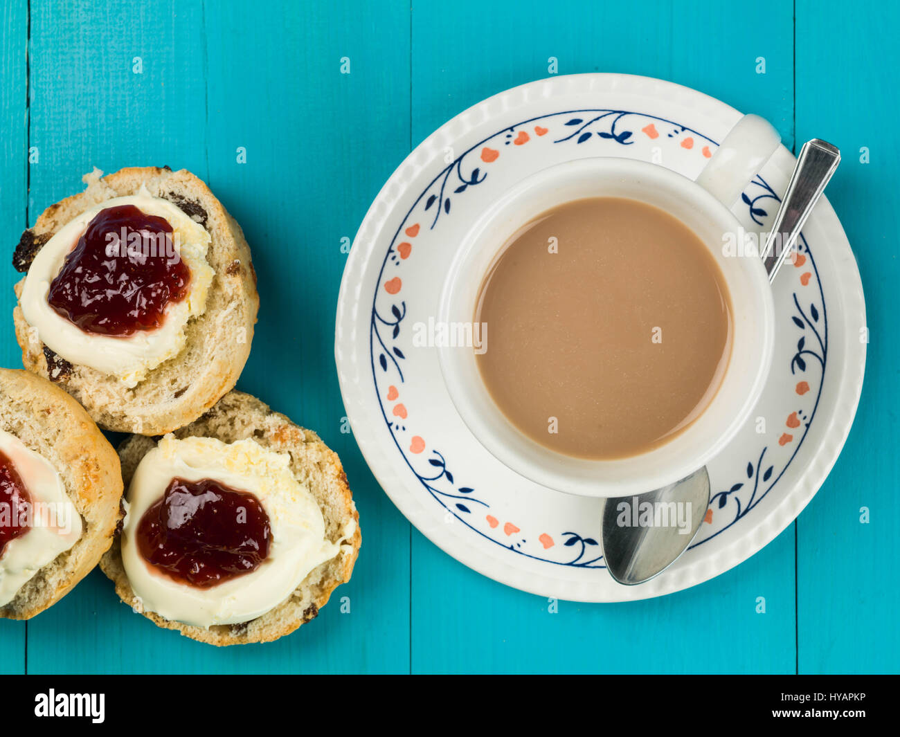 Cup of Tea or Coffee With Scones Clotted Cream and Strawberry Jam Against a Blue Background - Stock Image