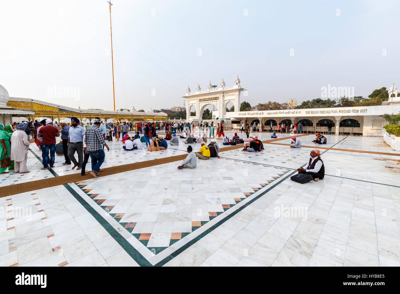 Marble paved courtyard and ornate arched entrance gate at Gurudwara Bangla Sahib, a Sikh temple in New Delhi, capital Stock Photo