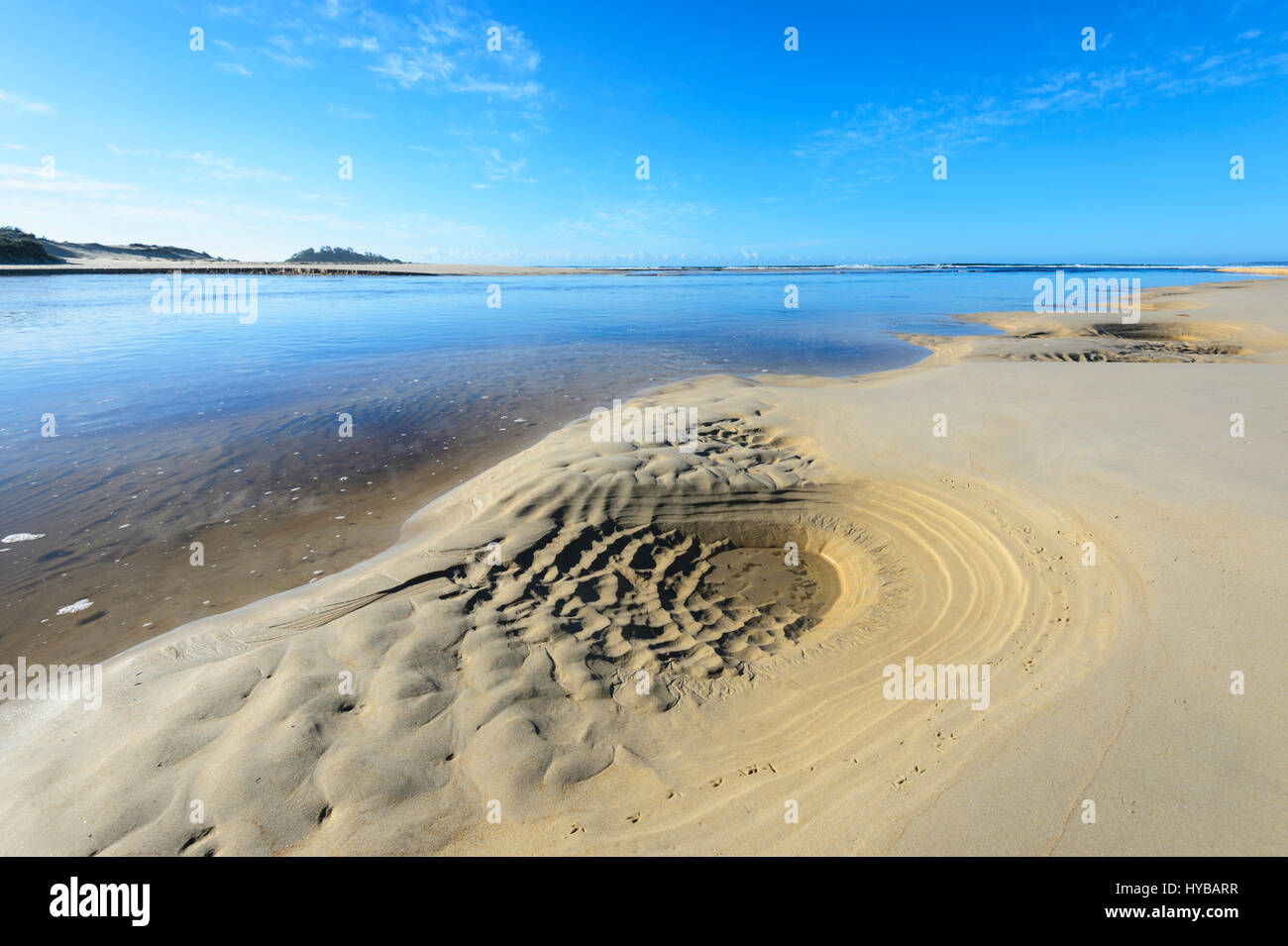 Sand patterns where Lake Conjola meets the sea at Conjola Beach, Shoalhaven, South Coast, New South Wales, NSW, - Stock Image