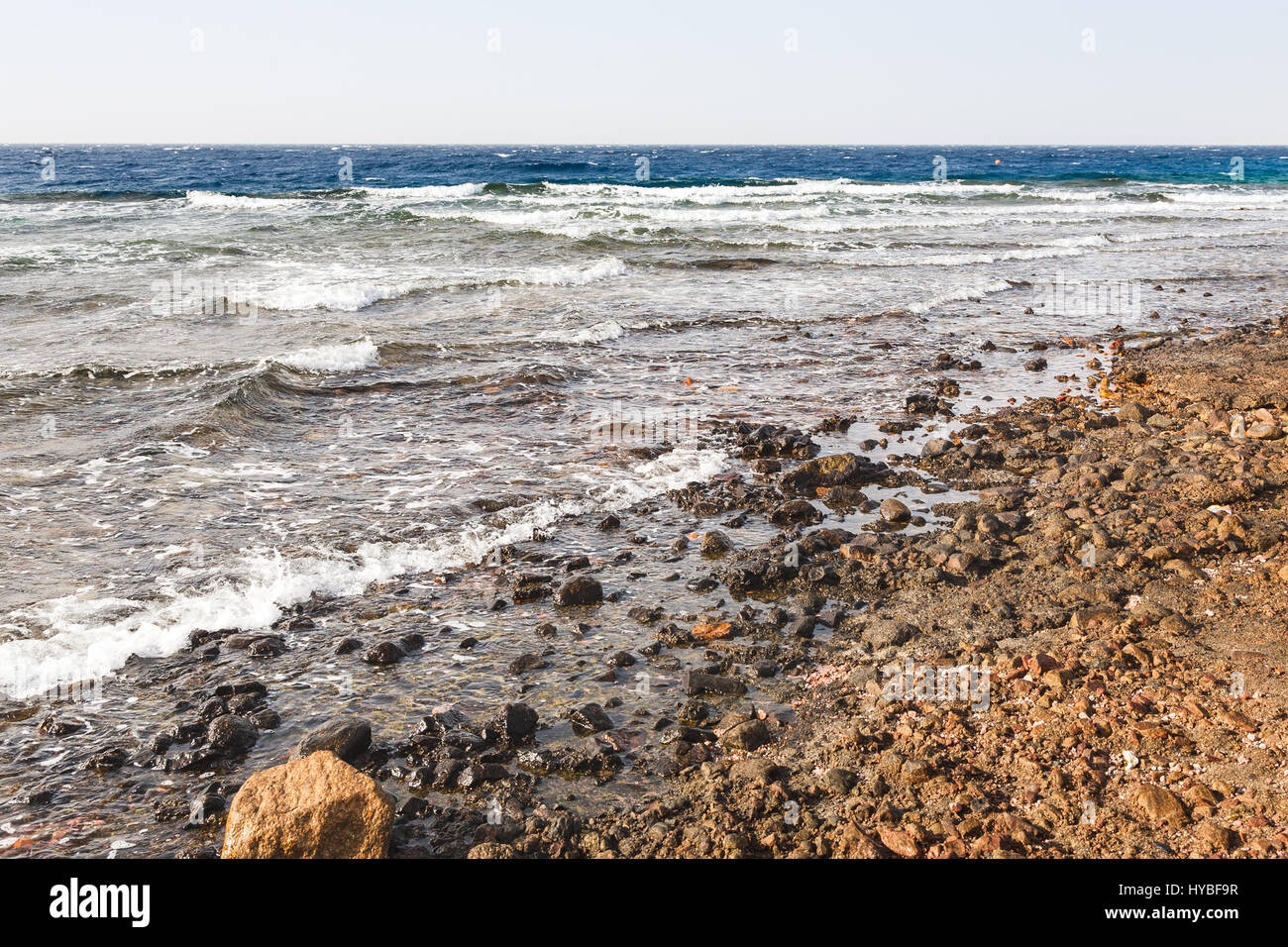 Travel to Middle East country Kingdom of Jordan - dirty beach near Aqaba port on Red Sea in winter - Stock Image
