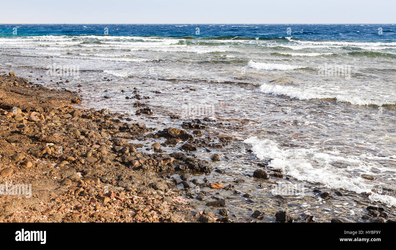 Travel to Middle East country Kingdom of Jordan - oil dirty beach near Aqaba city port on Red Sea in winter - Stock Image