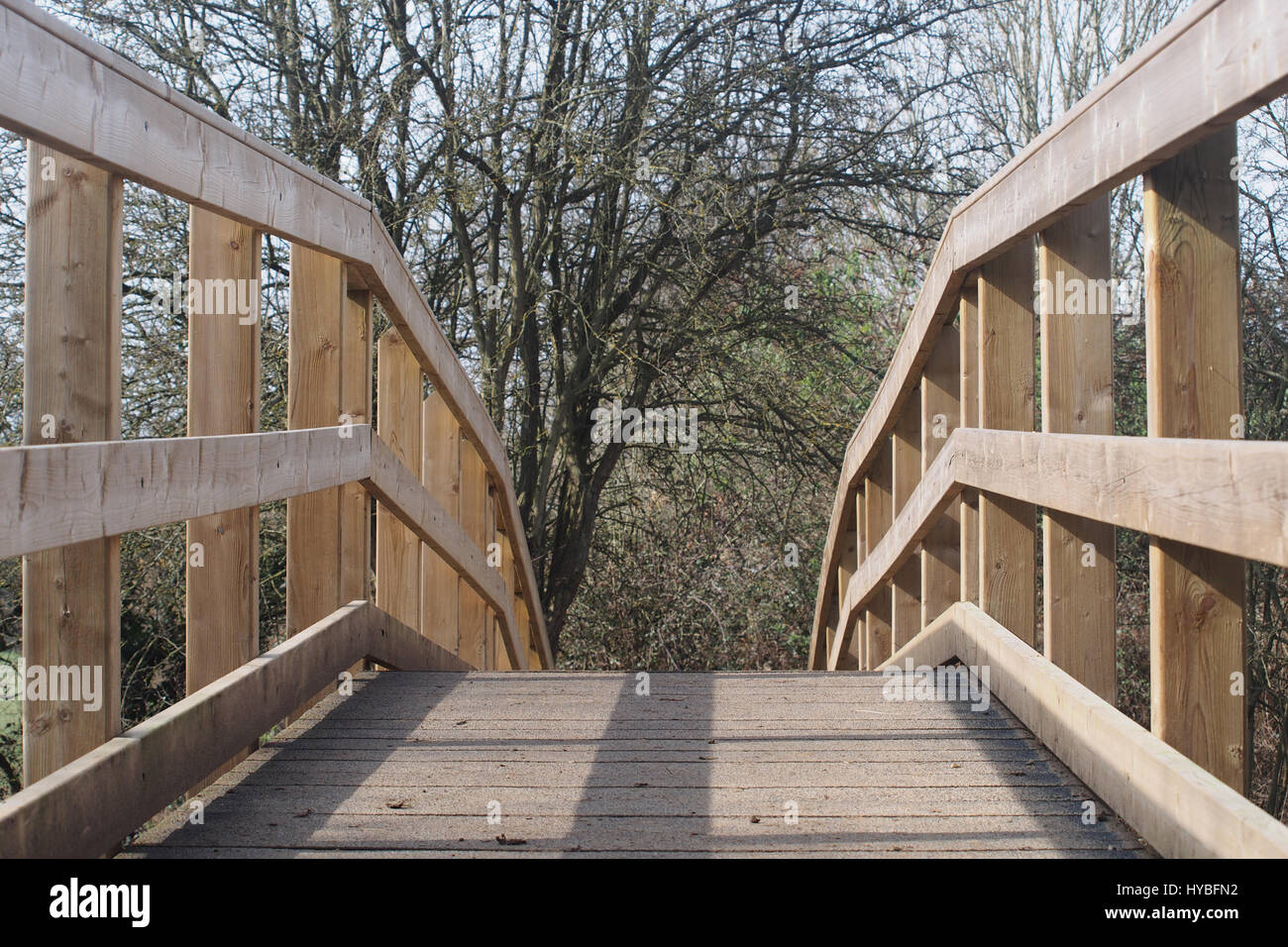 Sturdy wooden footbridge plus railings in  a country park - Stock Image