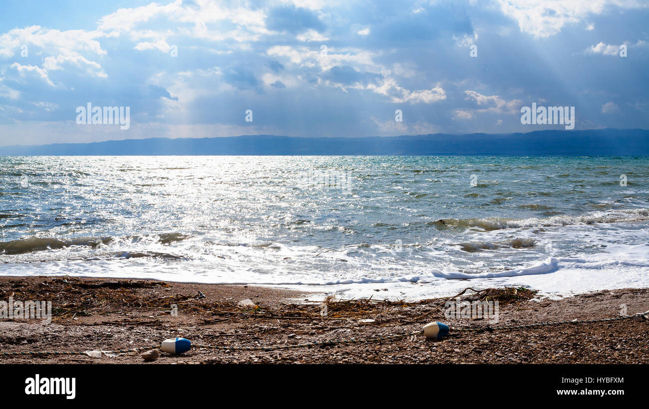 Travel to Middle East country Kingdom of Jordan - dirty beach of Dead Sea in cloudy winter day - Stock Image