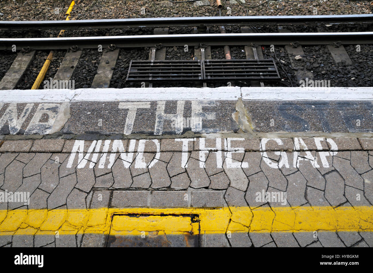 Mind The Gap painted on the edge of a train platform - Stock Image