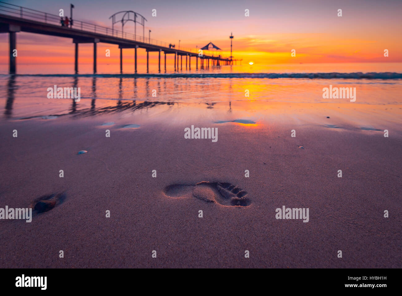 Human footprints in wet sand at sunset, South Australia - Stock Image