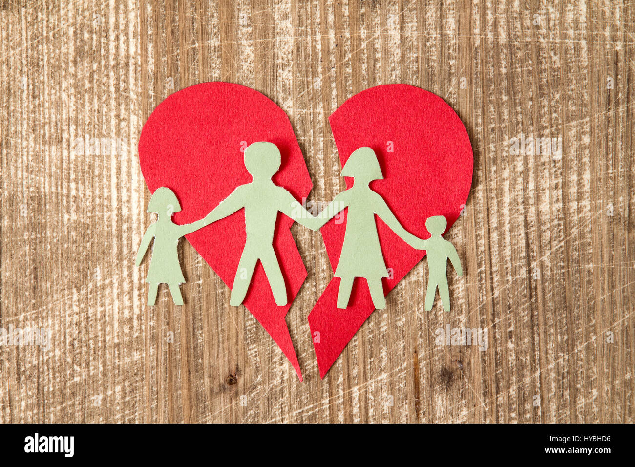 Paper family with broken heart on wooden table , divorce concept - Stock Image