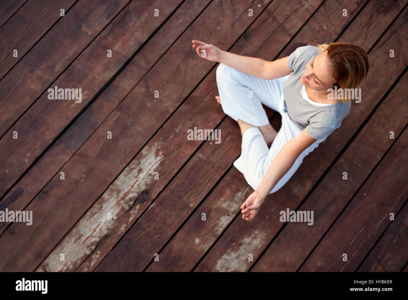 Woman Relaxing In Yoga Pose On Dock
