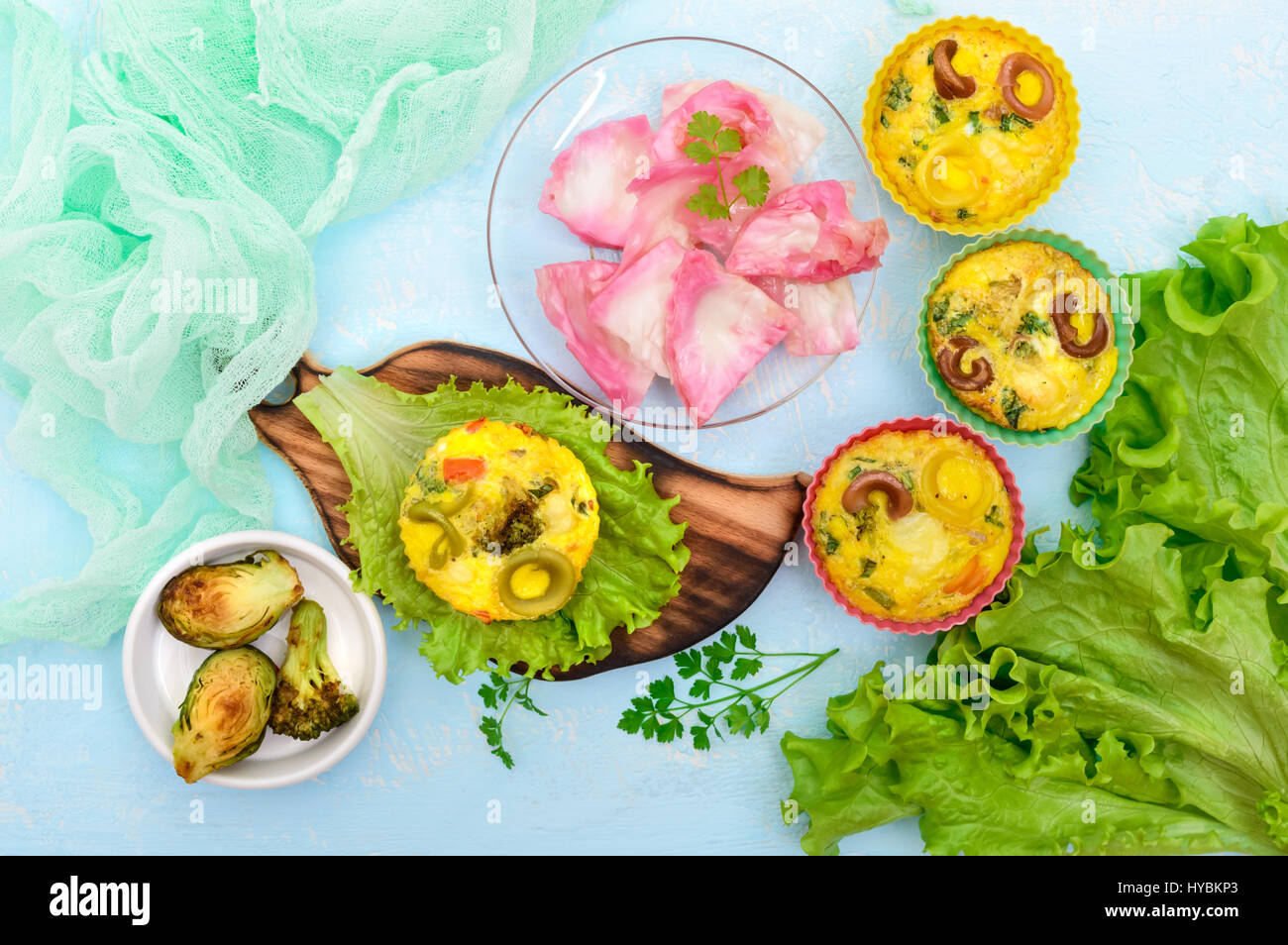 Omelette with colored pasta, mushrooms, vegetables and herbs, cooked in the form of mafins. The top view. Breakfast. - Stock Image